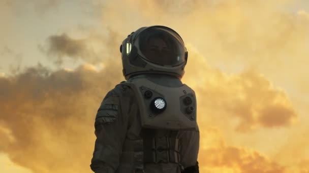 Niedrigen Winkel Schuss weibliche Astronauten im Raumanzug fremden Planeten umzusehen. Fortschrittliche Technologien, Raumfahrt, Kolonisation Konzept.
