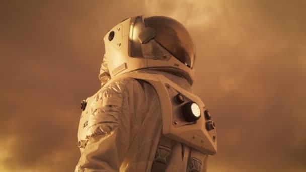 Niedrigen Winkel Schuss des tapferen Astronauten im Raumanzug fremden Planeten umzusehen. Rot und Orange Planet Mars ähnlich. Fortschrittliche Technologien, Raumfahrt, Kolonisation Konzept.