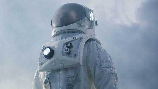 Niedrigen Winkel Schuss des tapferen Astronauten im Raumanzug fremden Planeten umzusehen. Planet blau aus und kalt. Fortschrittliche Technologien, Raumfahrt, Kolonisation Konzept.