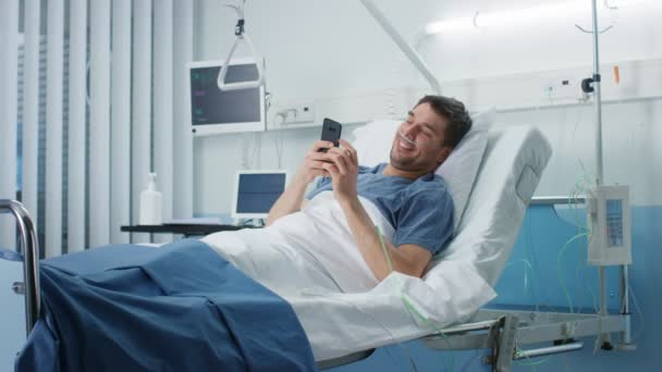Recovering Patient Uses Smartphone while Lying on a Bed in the Hospital. Friendly Nurse Comes in to Check on Him.