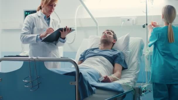 im Krankenhaus liegt männlicher Patient auf dem Bett, professionelle Ärztin schreibt in die Patientenakte, Krankenschwester überprüft Drop Counter und erhöht Dosis des Schmerzmittels.