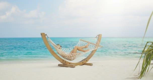 Idilli táj. Napozás függőágyban a parton fekvő gyönyörű nő. Azure Beach fehér homok és akvamarin vízzel. Süt a nap az egzotikus helyen.