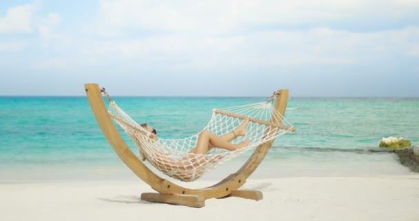 Idylická scéna. Krásná žena opalování leží v houpací síti na pláži. Azure Beach s bílým pískem a akvamarín vody. Slunce svítí na exotickém místě.