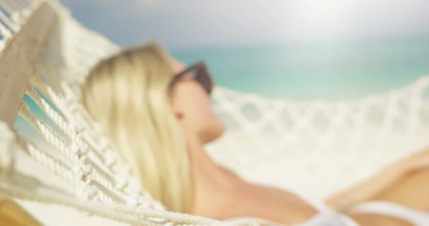Idilli táj. Közeli kép: egy gyönyörű szőke nő a napozás függőágyban a parton fekvő napszemüveg. Azure Beach fehér homok és akvamarin vízzel