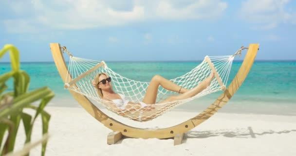 Idylická scéna. Krásná žena opalování leží v houpací síti na pláži. Azure Beach s bílým pískem a akvamarín vody. Slunce svítí na místě Exoric.
