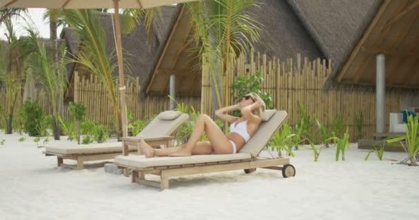 Krásná blondýna žena ležící na lehátku na pláži. Opalování na exotickém místě vily v pozadí.