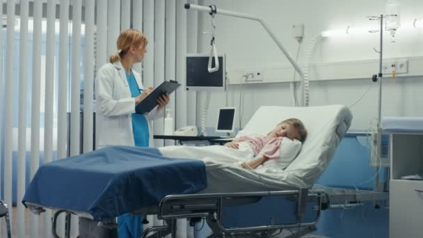 Sick Little Girl Lies on a Bed In the Hospital, Friendly Doctor Writes Medical Record/ Data into Clipboard, Talks with Nurse. Cute ill Child is Taken Care of in the Modern Pediatric/ Children Ward.