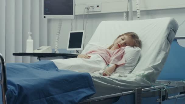 Das süße kleine kranke Mädchen schläft auf einem Bett im Kinderkrankenhaus. Moderne Kinderstation mit hochwertiger Gesundheitsversorgung.