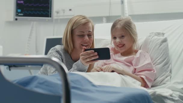 Nettes kleines Mädchen liegt auf einem Bett im Kinderkrankenhaus, ihre Mutter sitzt daneben, sie gucken Cartoons / lustige Videos auf dem Smartphone. Moderne Kinderstation.