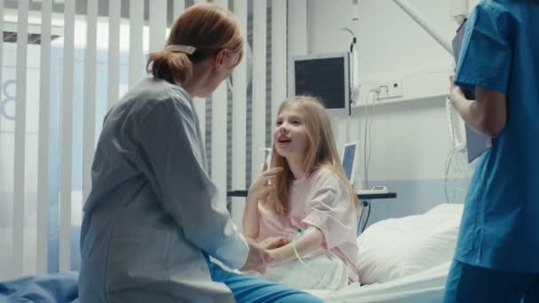 Niedliche kleine Mädchen sitzt auf einem Krankenhausbett und Gespräche mit freundliche Ärztin. Kinder Krankenhaus Kinderstation. Hochwertige medizinische Versorgung.