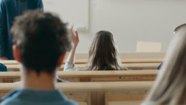 Hátulnézet a diákok az előadóterem, hallgató-hoz ad egy előadás professzor, egy diák emeli a kezét, és kéri a kérdés.