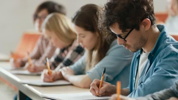 Řádek multietnické studentů ve třídě, přičemž zkoušky / Test / psaní v poznámkových blocích. Světlé mladých lidí studia na vysoké škole.