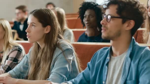 A tanterem Multi etnikai diákok hallgatni egy tanár és írás jegyzetfüzet. Intelligens fiatalok tanulmány az egyetemen.