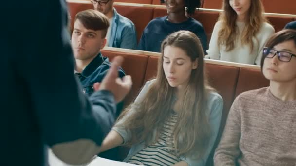 Camera Facing Class: College Professor Gives Lecture to a Classroom Full of Multi Ethnic Students. Lecturer Gesticulates with His Hands while Students Listen.