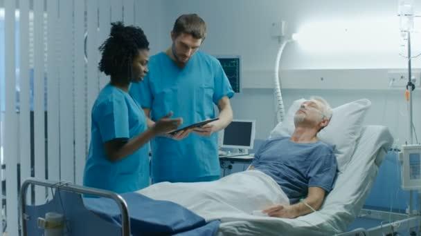 Im Krankenhaus liegt ein älterer Mann im Bett, spricht mit Arzt und Krankenschwester, die ihn mit einem Tablet-Computer diagnostizieren. Technologie hilft Kurpatienten, moderne Krankenhausstation.