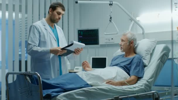 In the Hospital, Recovering Senior Patient Lying in Bed Talks with a Friendly Doctor. Modern Hospital Ward where People Get Best Health Care.