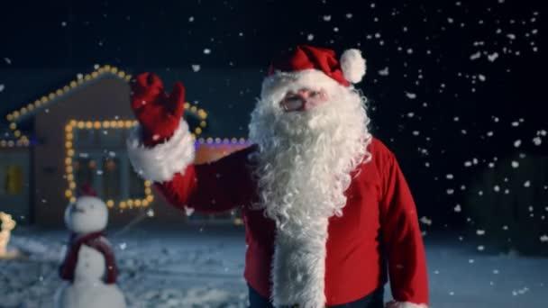 Portrét autentické Santa Claus, mávl rukou. Nový rok Eve Santa přináší radost, dárky a dárky pro každého. V pozadí domě ozdoben na Vánoce a padající sníh.