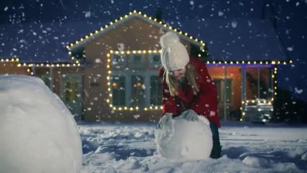 Aranyos kis lány, hogy egy hóe, guruló hógolyó. Gyermek a téli szórakozás, épít a hóember idilli ház-füzér és karácsonyfa a kertben.