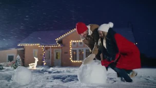 Boldog, fiatal pár teszi egy hóember, mind a járművek nagy hógolyó. Családi szórakozás egy téli estén. A háttér házban díszített koszorúkat.