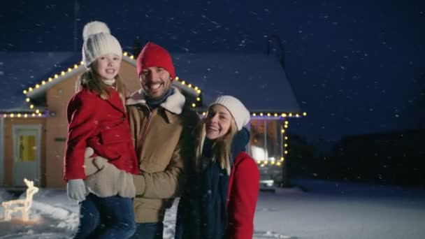 Boldog fiatal családi portré a hóesésben, apja ölel felesége és lánya tartja. Családi élvezi téli üdülés a idilli ház díszített koszorúkat elülső udvarán.