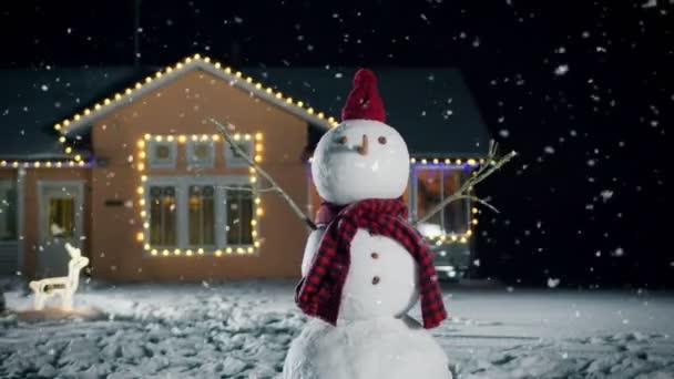 Lustiger Schneemann mit Hut und Schal steht an Heiligabend im Hinterhof des idyllischen Hauses, das mit Girlanden geschmückt ist. Weicher Schnee fällt an diesem magischen Winterabend.