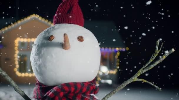Nahaufnahme des lustigen Schneemanns mit Hut und Schal, der an Heiligabend im Hinterhof des idyllischen, mit Girlanden geschmückten Hauses steht. Schnee fällt an diesem magischen Winterabend.
