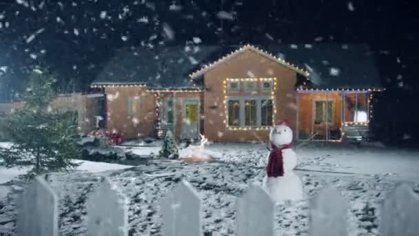 Felvétel az idilli ház díszített koszorúkat, karácsony, hóember, karácsonyfa, áll az első udvar. Gyönyörű téli este lágy hóesésben.