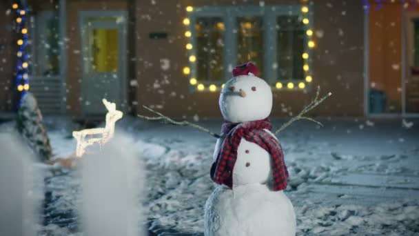 Legrační sněhulák nosí čepici a šálu, stojící v zahradě idylické domu zdobí věnce na Štědrý den. Měkký sníh padá na kouzelné Zimní večer.