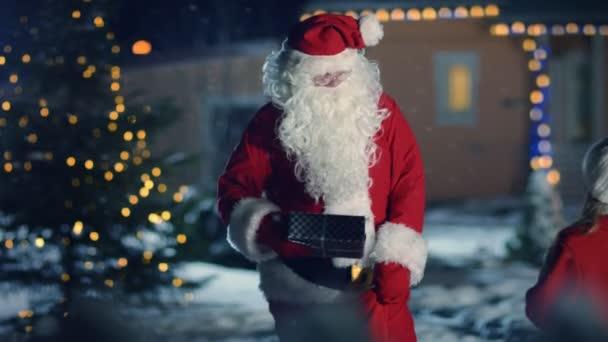 Hiteles Mikulás keresztkötés ajándék doboz és ad ez egy aranyos kislány. A háttérben, idilli díszített Front Yard, hóember, karácsonyfa és idilli ház. Varázslatos Szilveszter.