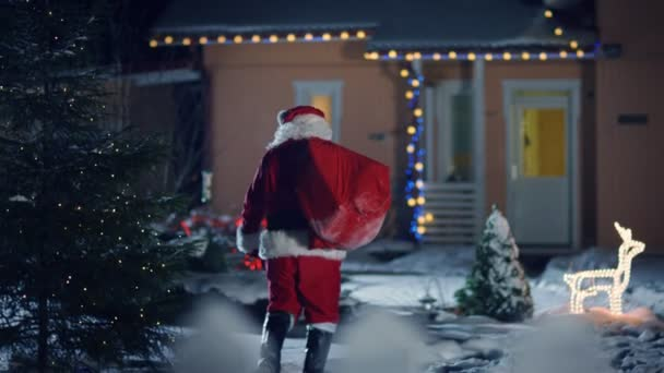Authentic Santa Claus Carrying Red Bag over the Shoulder, Walks into Front Yard of the Idyllic House Decorated with Lights and Garlands. Santa Bringing Gifts and Presents. Magical New Years Eve with Falling Snow.