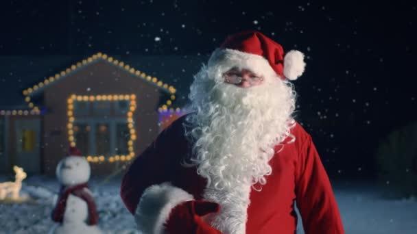 Hiteles Mikulás portréja, szívből nevet, és bólint. Készen áll a New Years Eve, hogy öröm, ajándékok, és jelent mindenki számára. A háttér ház díszített karácsonyi és hóember állt az első udvarban.