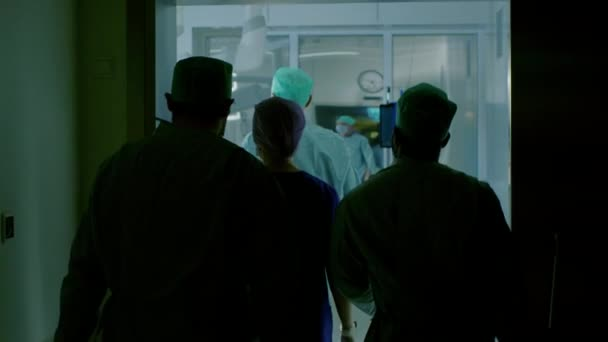 Following Shot of Diverse Team of Surgeons and Assistants Walk into Operating Room Where Patient Waits, they put Him under Anesthesia and Start Surgery. Real Modern Hospital with Authentic Equipment.