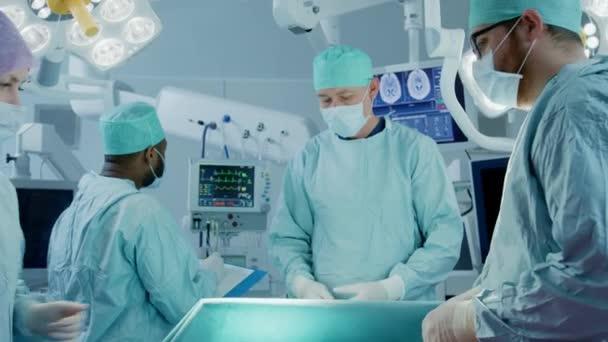 Ein Team professioneller Chirurgen führt invasive Operationen an einem Patienten im Operationssaal des Krankenhauses durch. Krankenschwester reicht dem Chirurgen Instrumente, Anästhesist überwacht Vitalstoffe. modernes Krankenhaus.