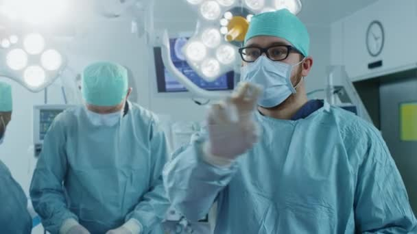 Im Operationssaal Chirurgengesten mit Augmented Reality Technologie während der Operation. Im Hintergrund Assistenten und Krankenschwestern, die mit Real Equipment arbeiten.