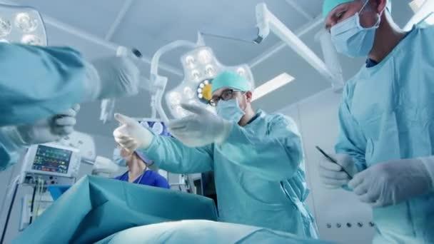 Vielfältiges Team professioneller Chirurgen, die invasive Operationen an einem Patienten im Operationssaal des Krankenhauses durchführen. Einsatz von Chirurgen und anderen Instrumenten.
