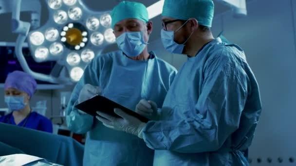 Professionelle Chirurgen und Assistenten sprechen und nutzen digitale Tablet-Computer im Stehen im modernen Operationssaal eines Krankenhauses.