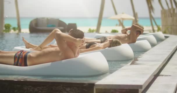Three Beautiful Young People Sunbathing on the Pool Mattresses. Azure Beach with White Sands and Aquamarine Water. Sun Shines on the Exotic Location.