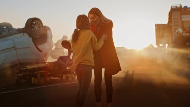 Zraněná matka a mladá dcera se znovu shledají po hrozné dopravní nehodě, šťastně se obejmou. V pozadí prostřednictvím kouře a ohně, odvážní zdravotníci a hasiči zachránit životy