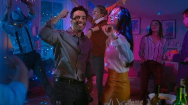 At the College House Costume Party: Beautiful Girl and Boy Dance Together, in the Background Diverse Crowd of Young People Have Fun, Dancing, Jumping, Socializing and Drinking. Neon Lights.