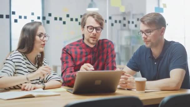 Giovane donna e due colleghi maschi che hanno una riunione amichevole e discutono di nuove idee di business. Easygoing Coworking Atmosphere in Loft Office Creative Agency. Prendono appunti in notebook e tablet.
