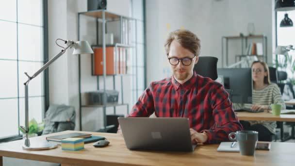 Schöner junger Mann mit Brille und Hemd arbeitet in einer Kreativagentur an einem Laptop. Sie arbeiten im Loft Office. Diverse Menschen, die im Hintergrund arbeiten. Er ist gut drauf.