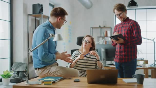 Slow Motion Shot of Young Woman and Two Male Colleagues Having a Friendly Meeting and Discussing New Business Ideas. Easygoing Coworking Atmosphere in Loft Office Creative Agency.