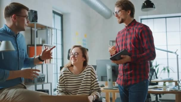 Young Woman and Two Male Colleagues Having a Friendly Meeting and Discussing New Business Ideas. Easygoing Coworking Atmosphere in Loft Office Creative Agency. They Celebrate a Successful Solution.