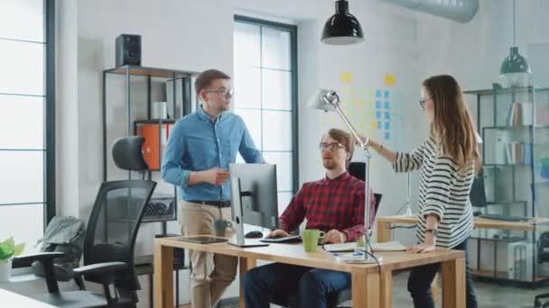 Giovani colleghi professionisti che hanno una riunione amichevole e discutono di nuove idee di business. Easygoing Coworking Atmosphere in Loft Office Creative Agency. Fanno note su computer e tablet.