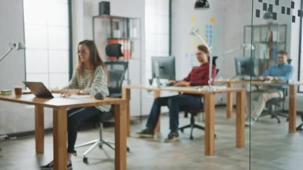 Rozmazaný záznam života tvůrčí agentury. Ženská kolegyně pracuje se dvěma mužským spolupracovníkem za stolem. Koncepce Creative Office. Pracují v počítačích a v noteboocích..