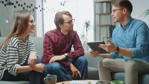Giovane donna e due colleghi maschi che hanno una riunione amichevole e discutono di nuove idee di business. Easygoing Coworking Atmosphere in Loft Office Creative Agency. Guardano carte e tablet.