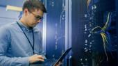 V datovém centru stojí inženýr před pracovním stojanem na pracovní server provedení rutinní údržby kontrola a diagnostika pomocí přenosného počítače. Viditelné počítačové hardwarové vybavení, LED indikátory širokopásmových optických vláken.