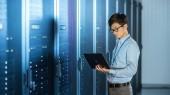 V moderním datovém středisku: inženýr, stojící vedle stojanových skříní serveru, neprovádí bezdrátovou údržbu a diagnostiku s přenosným počítačem.