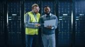 Vousatý černý inženýr stálý a usměvavý uprostřed pracovního centra pracovních dat se serverovými počítači pracně na stojanu.