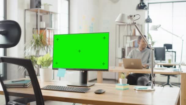 Stolní počítač s počítačovou obrazovkou stojí na stole v moderní tvůrčí kanceláři. Na pozadí v kanceláři, kde pracuje rozmanitý tým mladých profesionálů na počítačích